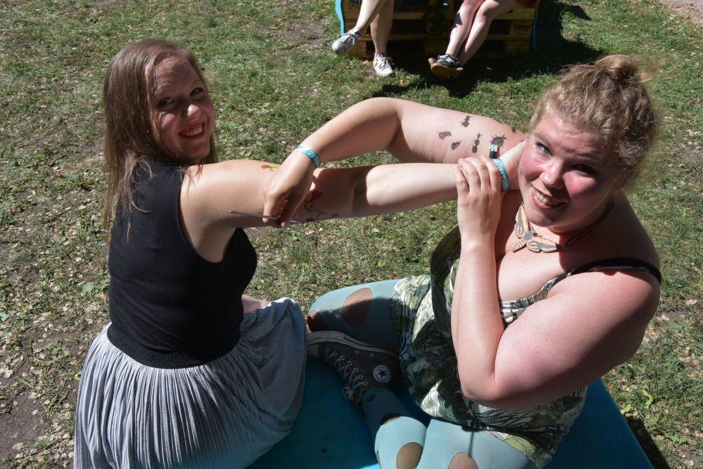 Två kvinnor målar med ansiktsfärger på varandras armar.