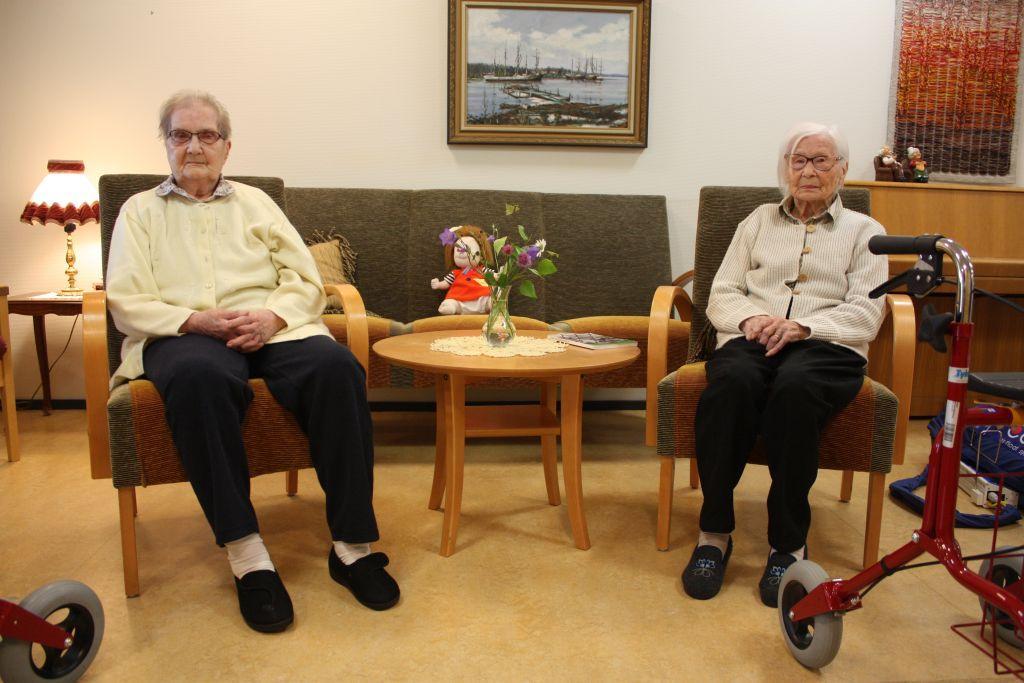 Margit Karlsson och Violet Åhlfors sitter i varsin stol, mellan dem står ett litet runt bord, i bakgrunden en grön soffa och en tavla på väggen