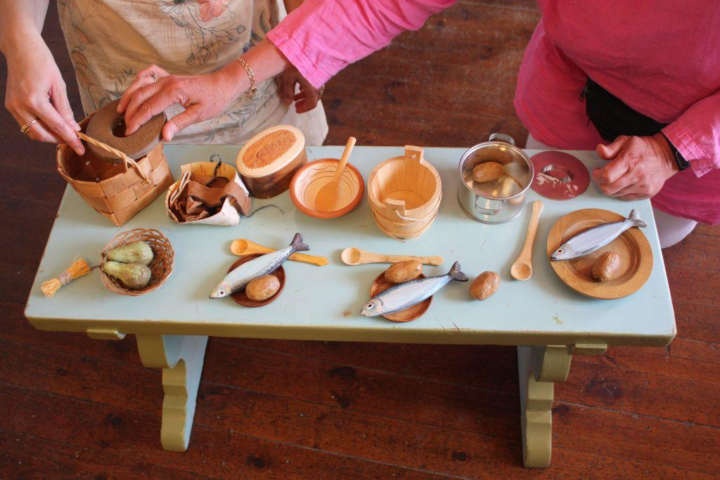 Litet dukat bord fotat uppifrån, husgeråd och föremål som föreställer råvaror på.