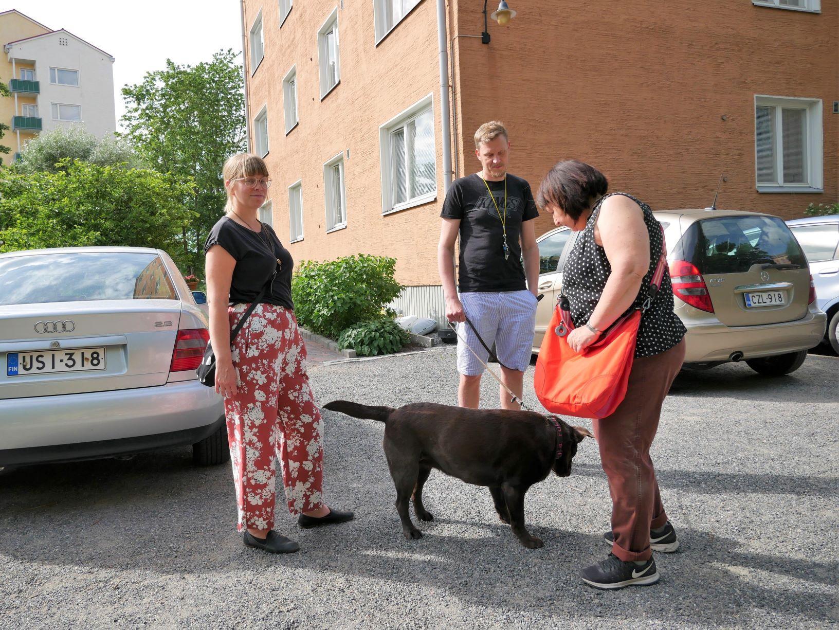 tre personer står och pratar på en parkeringsplats