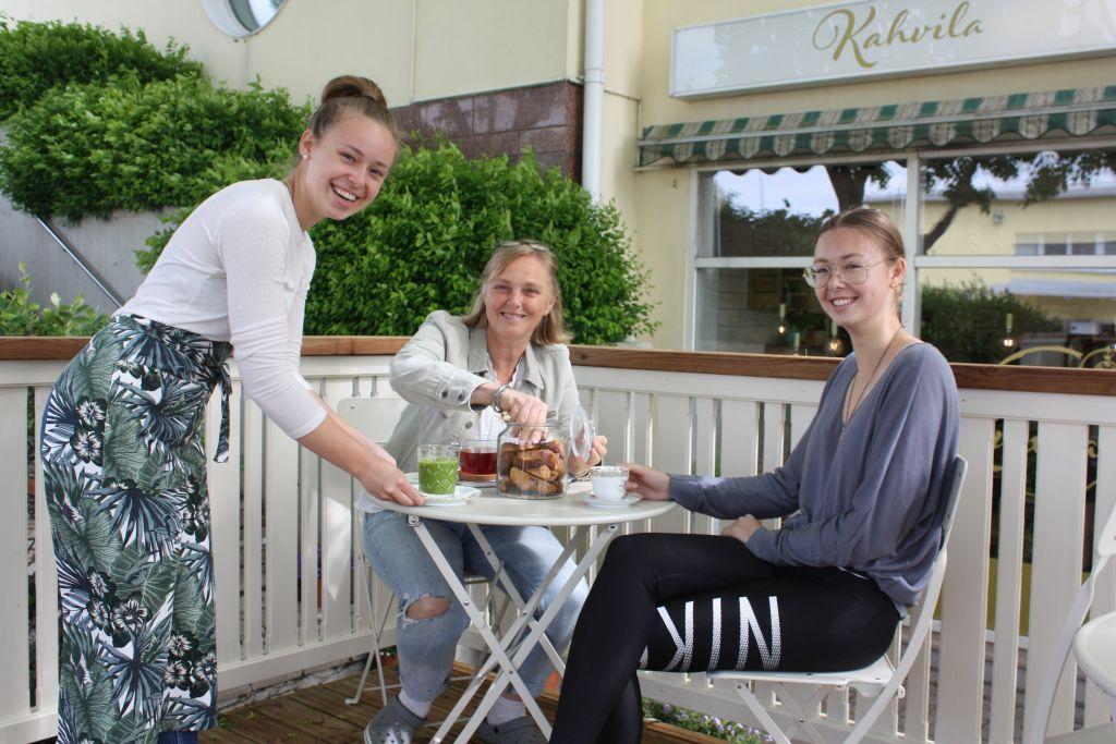 Cecilia, Weckström står bredvid ett vitt runt bord som Nina Björkman och Wilma Weckström sitter vid, i bakgrunden en byggnad och gröna buskar