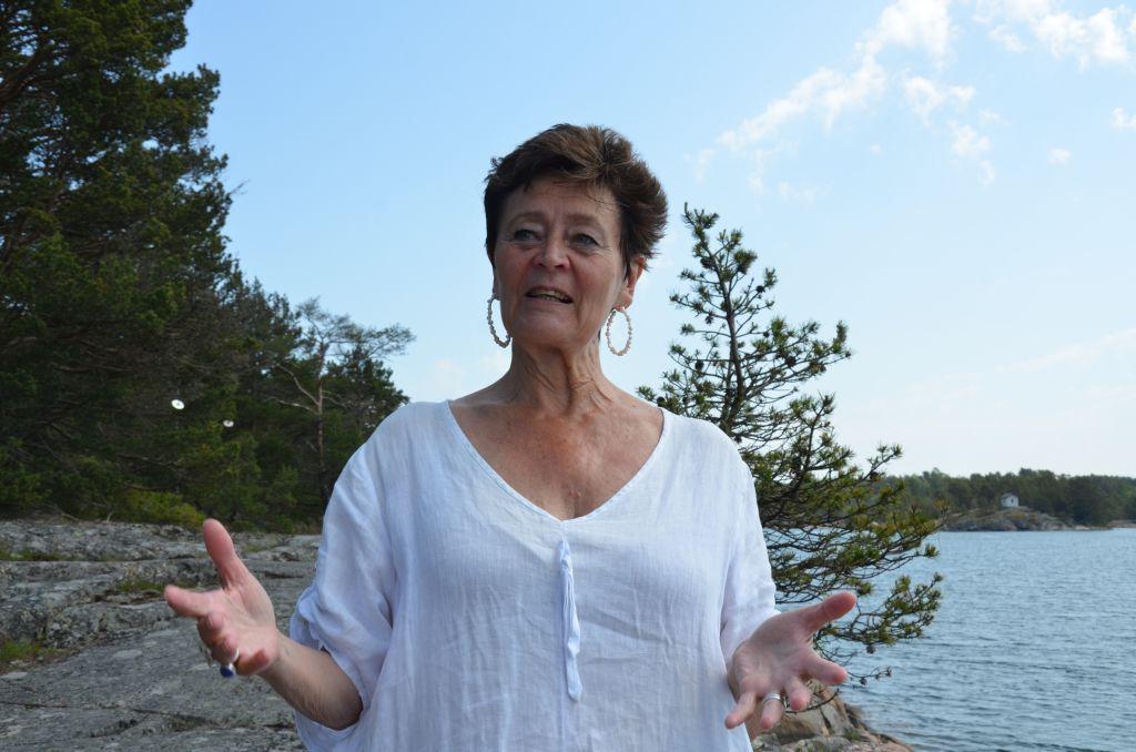 En kvinna klädd i vitt står och gestikulerar på ett berg. I bakgrunden syns havet.