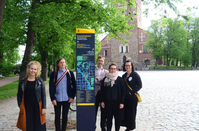 En del av arbetsgruppen bakom projektet står invid den nya skylten vid Domkyrkotorget.