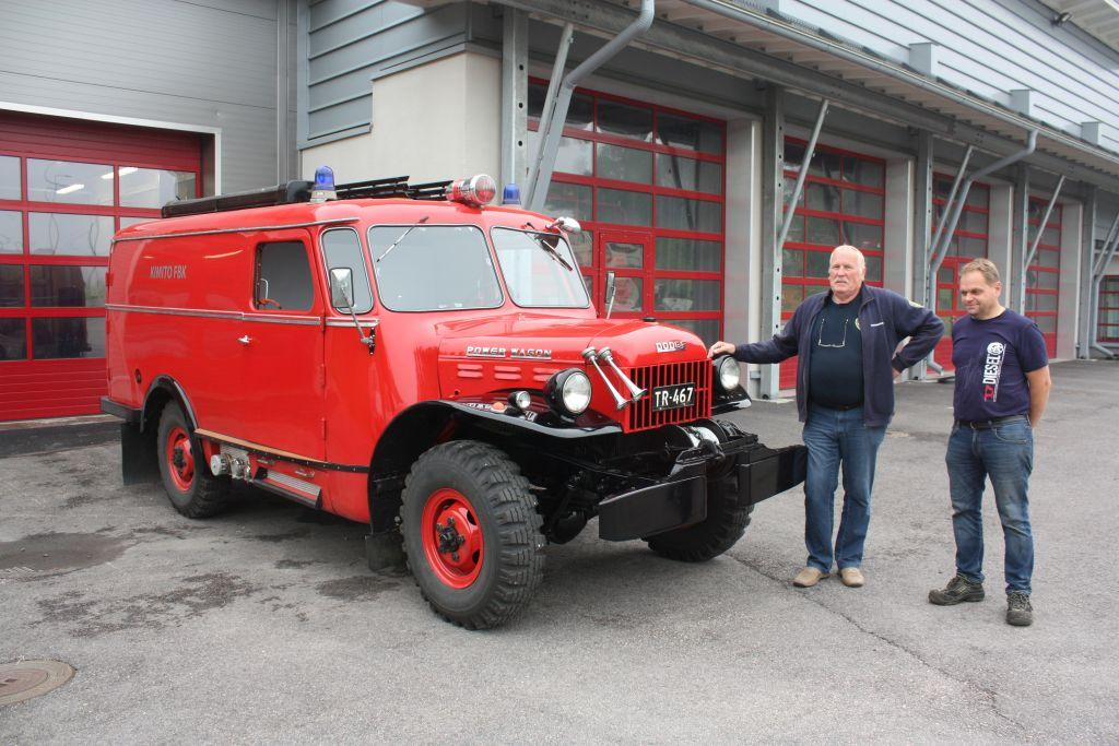 Röd brandbil från 1940-talet, bredvid står Per Sundström och Hasse Korsström, Kimito brandstation i bakgrunden