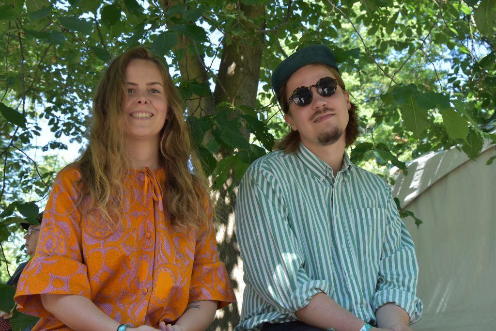 En ung kvinna och en ung man sitter under ett träd.