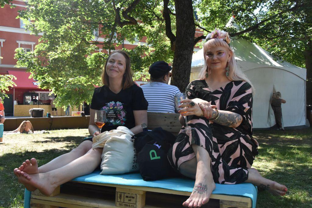 Två kvinnor sitter på lastpallar som gjorts om till soffor med varsitt vinglas i handen