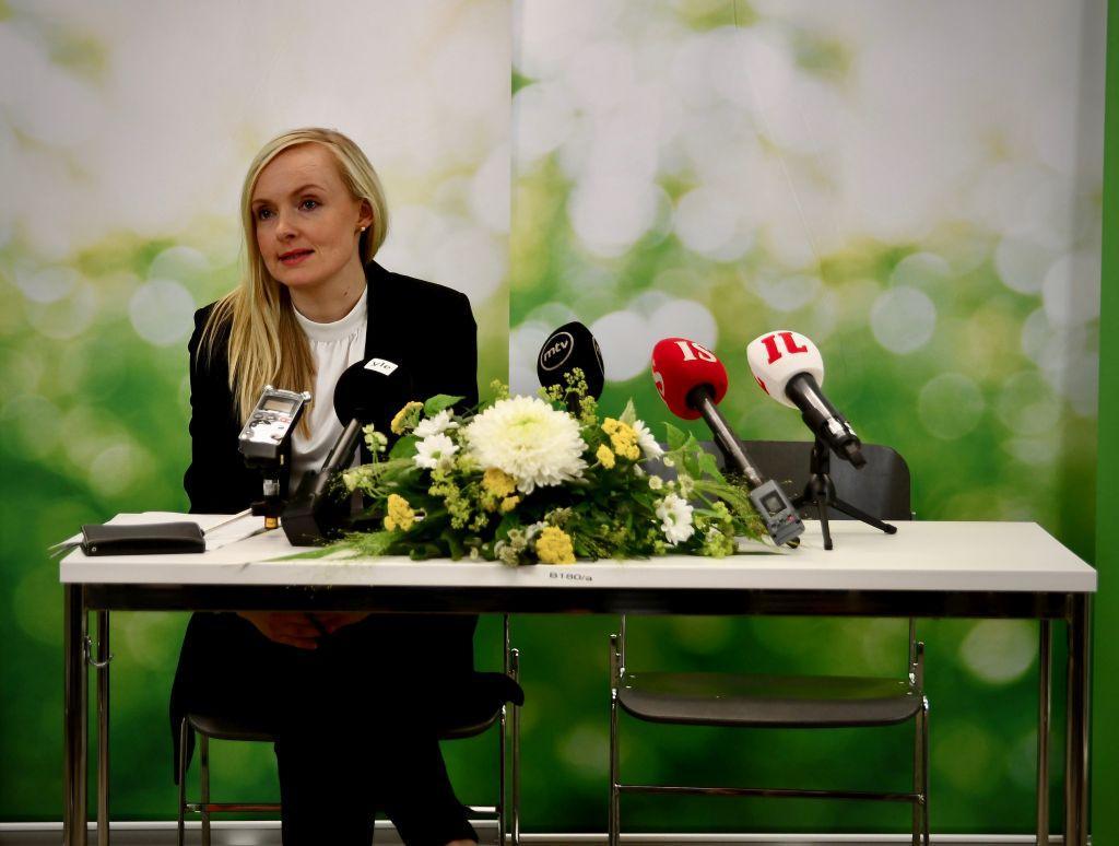 Kvinna sitter vid ett bord med blommor och mikrofoner