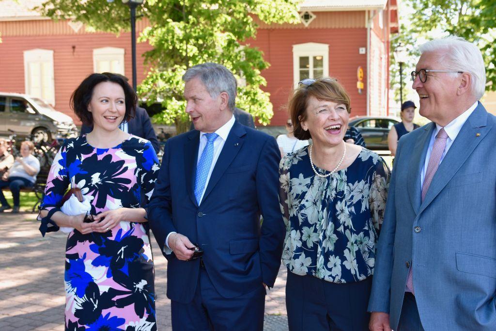 Fyra personer skrattar och tittar på varandra utomhus