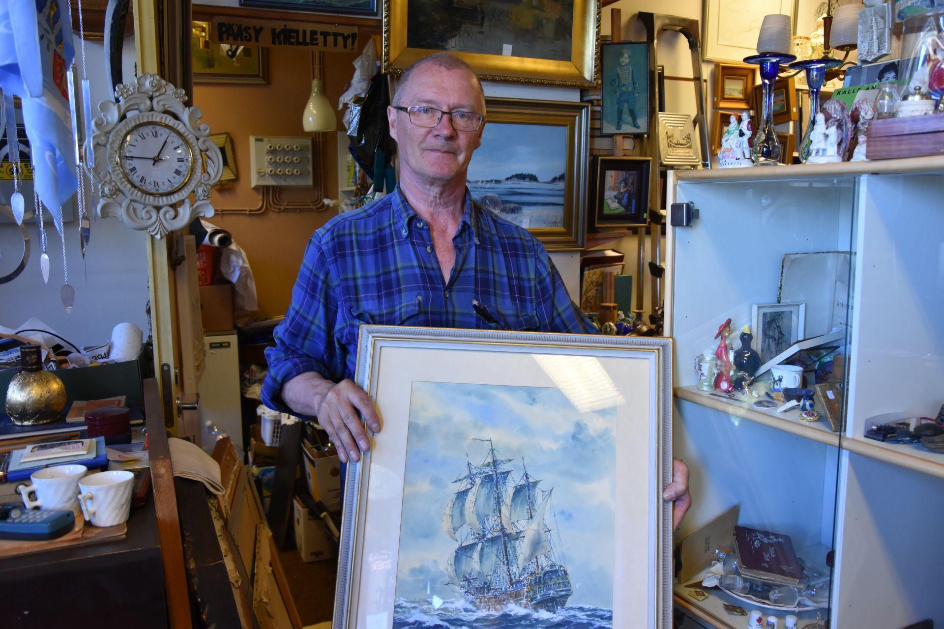 En man står i en affär med hyllor fyllda av prydnadsföremål och i bakgrunden hänger tavlor. I handen har mannen en tavla av ett skepp.