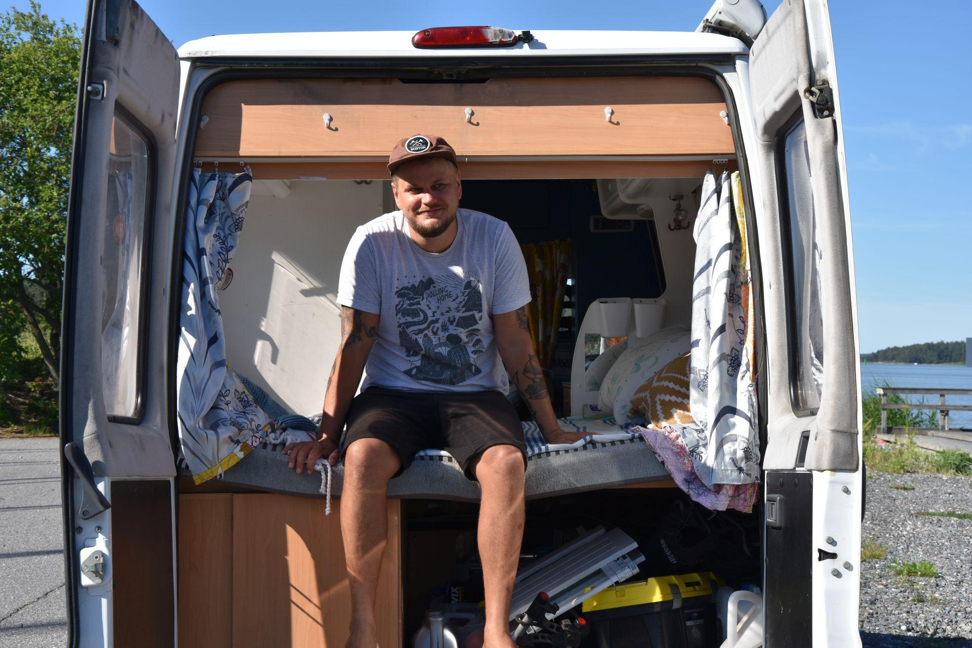 En man klädd i shorts, t-skjorta och keps sitter på en säng som finns i den öppna bakluckan av en paketbil.