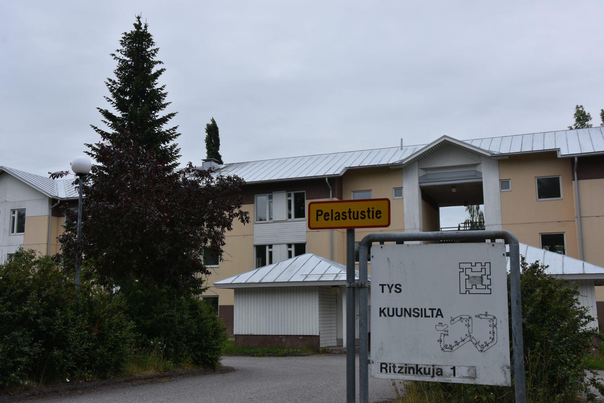 En skylt med en karta över Kuunsilta-bostadskomplexet och Studentbystiftelsens logotyp framför ett trevåningshus.