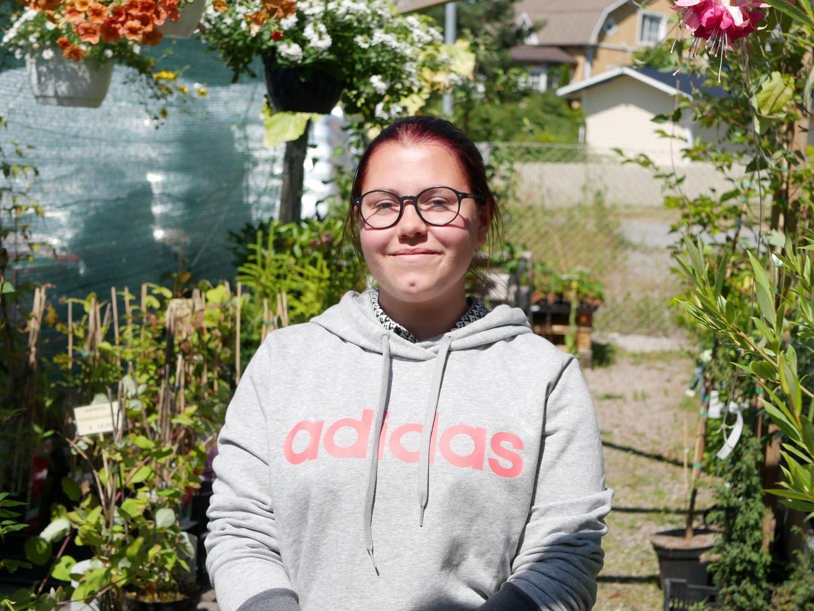 Person står med växter i bakgrunden
