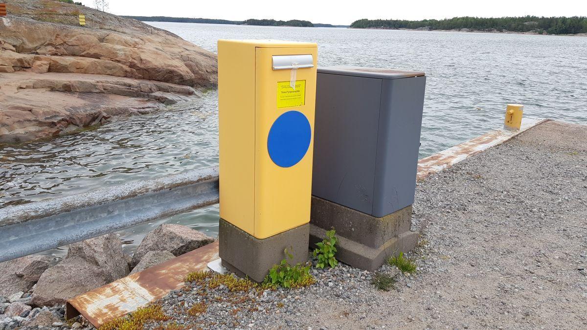 Postlåda på en strand, havet syns bakom