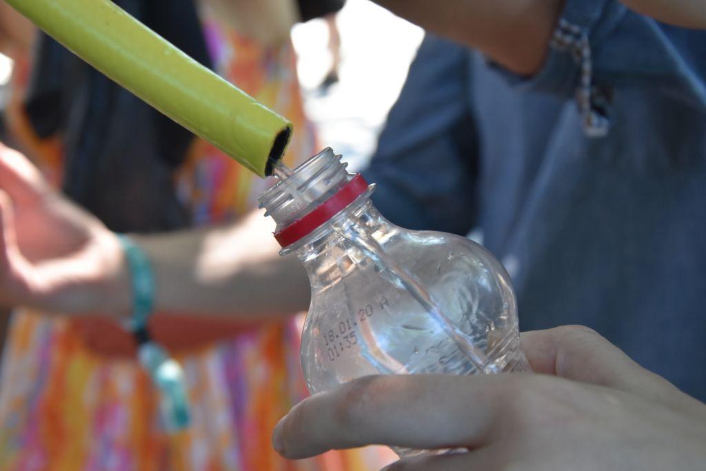 en vattenflaska fylls med vatten ur en slang