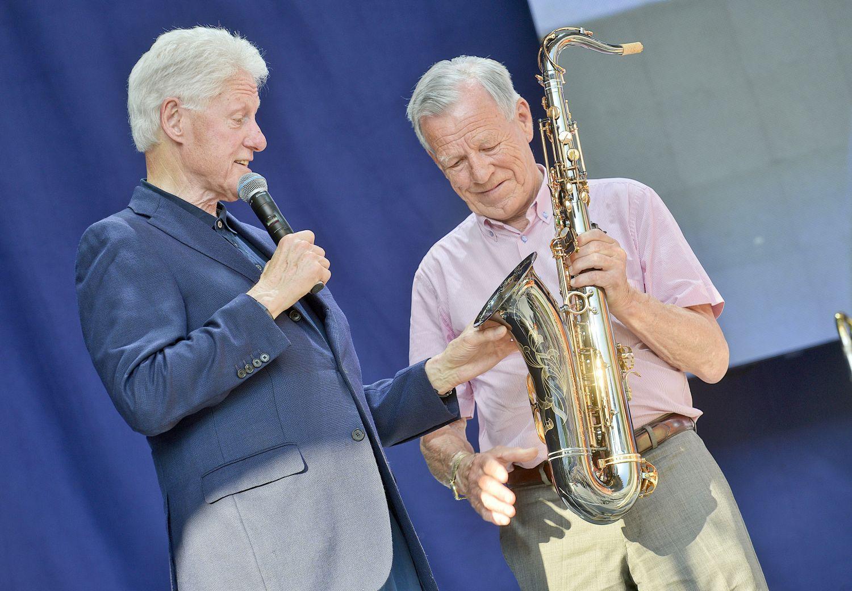 Bill Clinton och Anders Wiklöf står på en scen. Wiklöf överräcker en saxofon till Clinton.