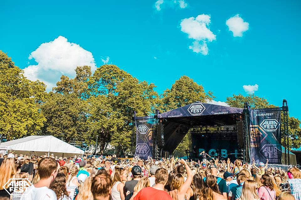 Bild på en festivalpublik som står framför en scen i kuppisparken i solskenet.
