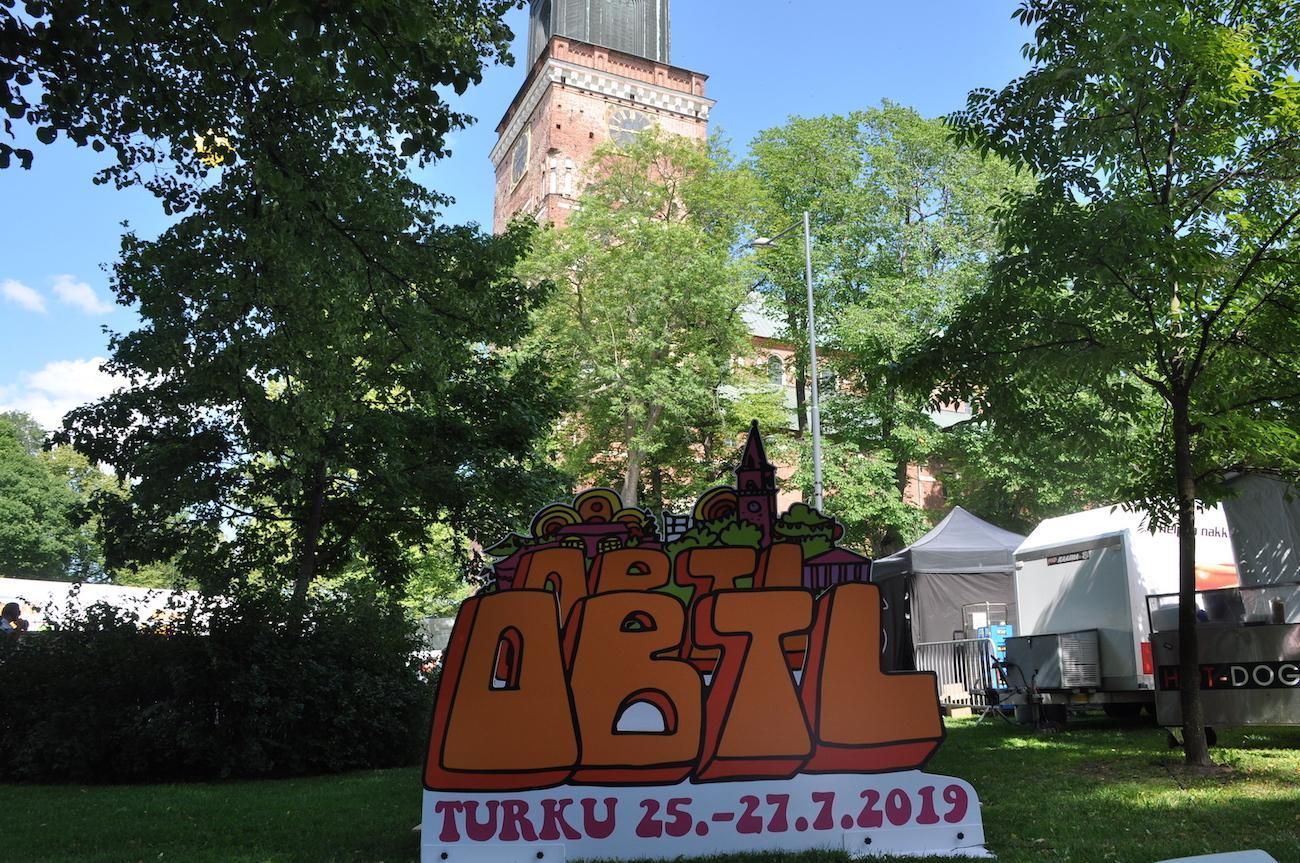 En skylt för festivalen fotad med domkyrkan i bakgrunden.