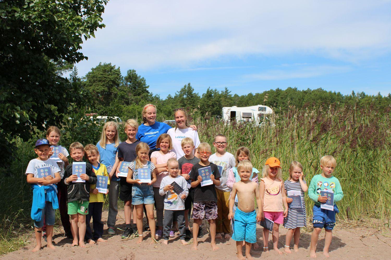 17 barn håller i sina simskolediplom på den soliga sandstranden. Simläraren och lekledaren står bakom dem.