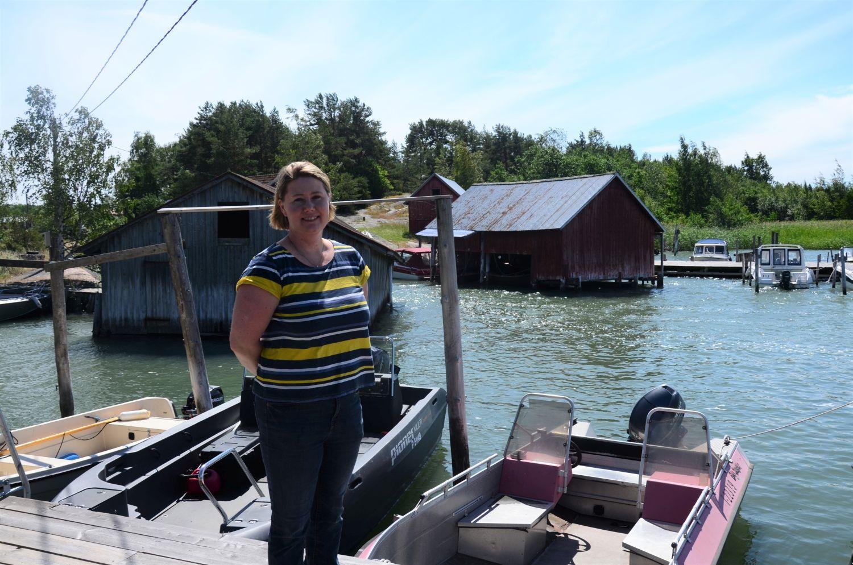 Tiina Pöyli på Jumo bystrand. I bakgrunden syns trähus och båtar vid bryggorna.