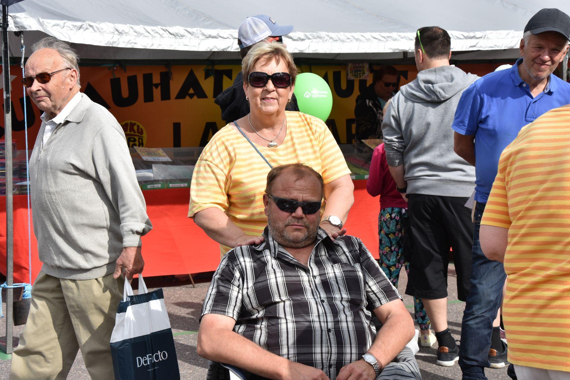 En man sitter i en stol och blir masserad av en kvinna. I bakgrunden rör sig människor.