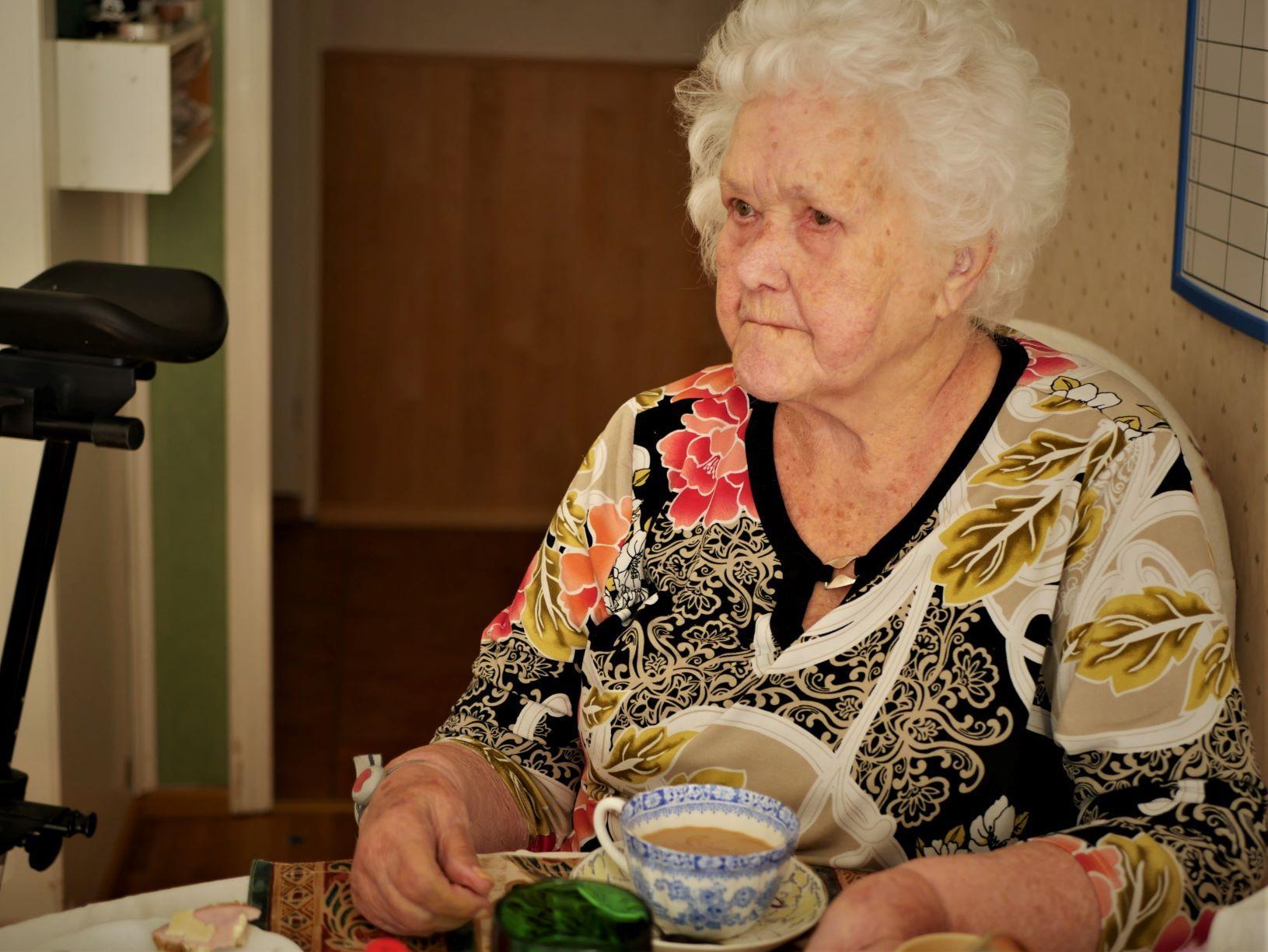 Äldre kvinna dricker kaffe