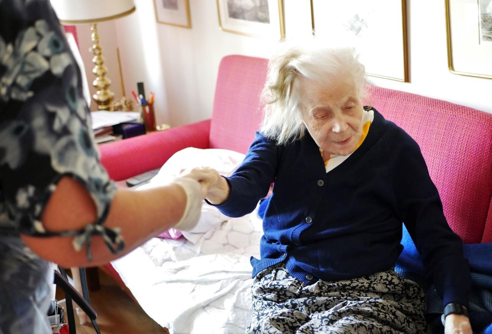 Vårdare håller i äldre persons hand och drar upp henne ur sängen