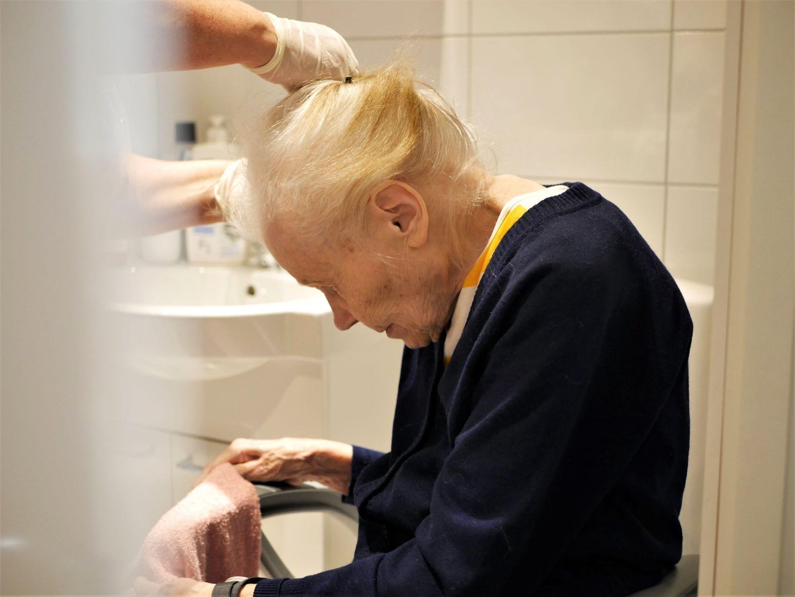 äldre kvinna får håret uppsatt.