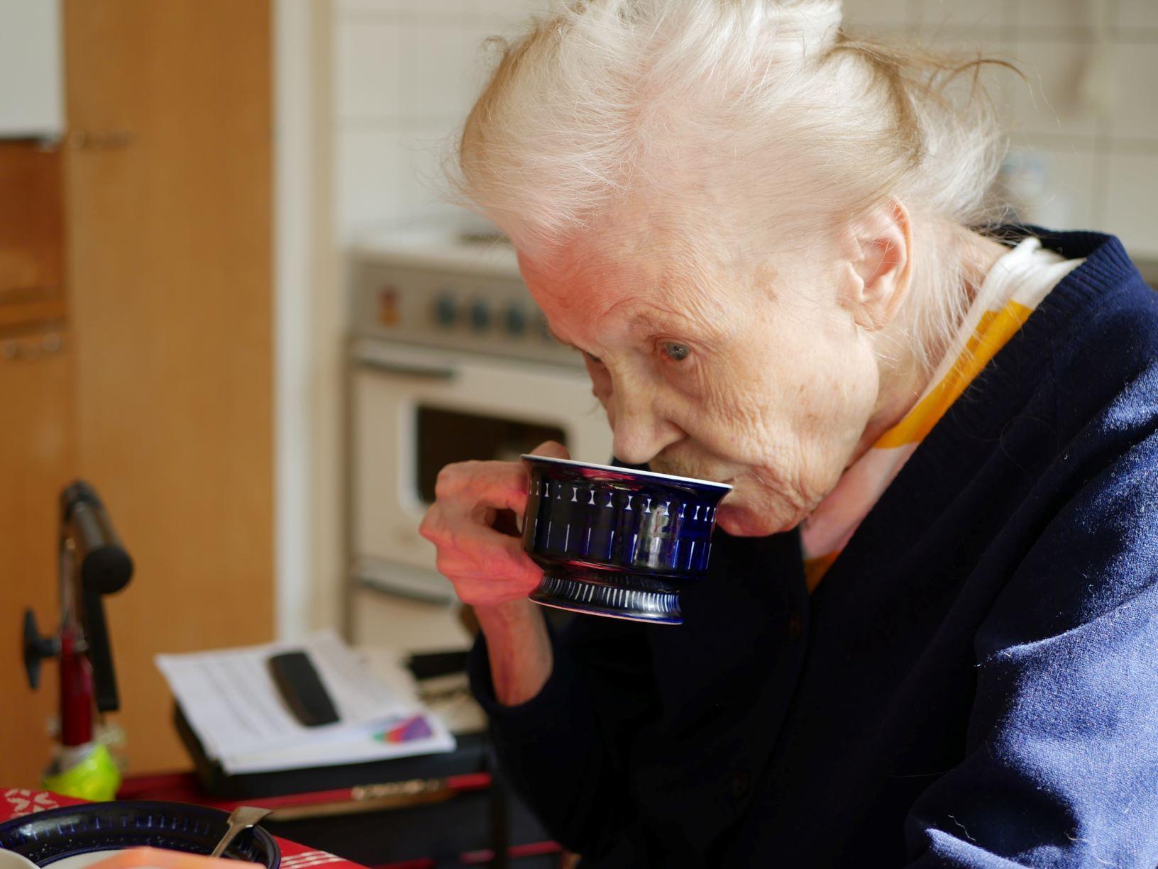 Äldre kvinna dricker kaffe i köket