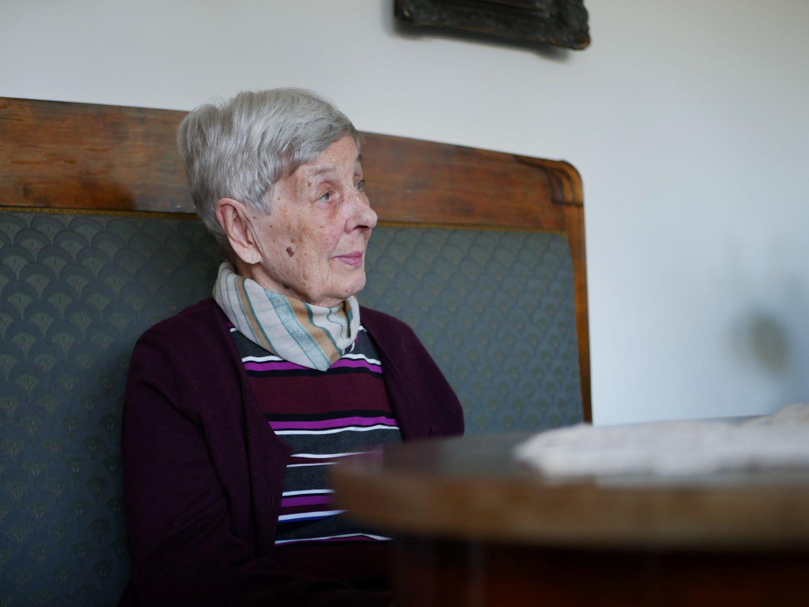 En äldre dam sitter i en gammal soffa