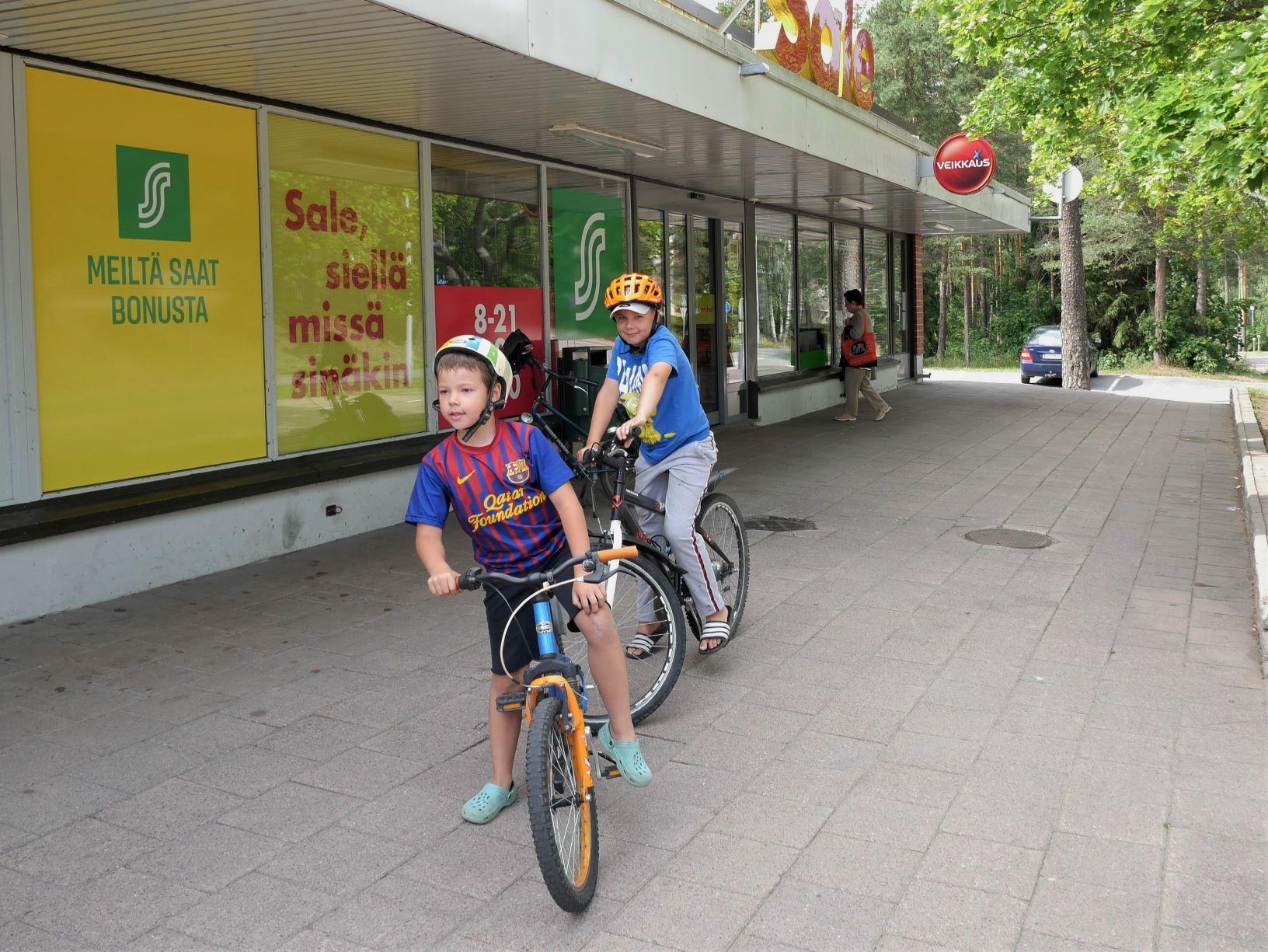 Två pojkar står på sin cykel utanför matbutik
