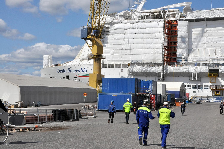 fartygsarbetare med fartygsbygge i bakgrunden