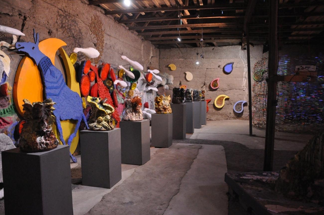Olika konstverk av keramik upprada på ett galleri