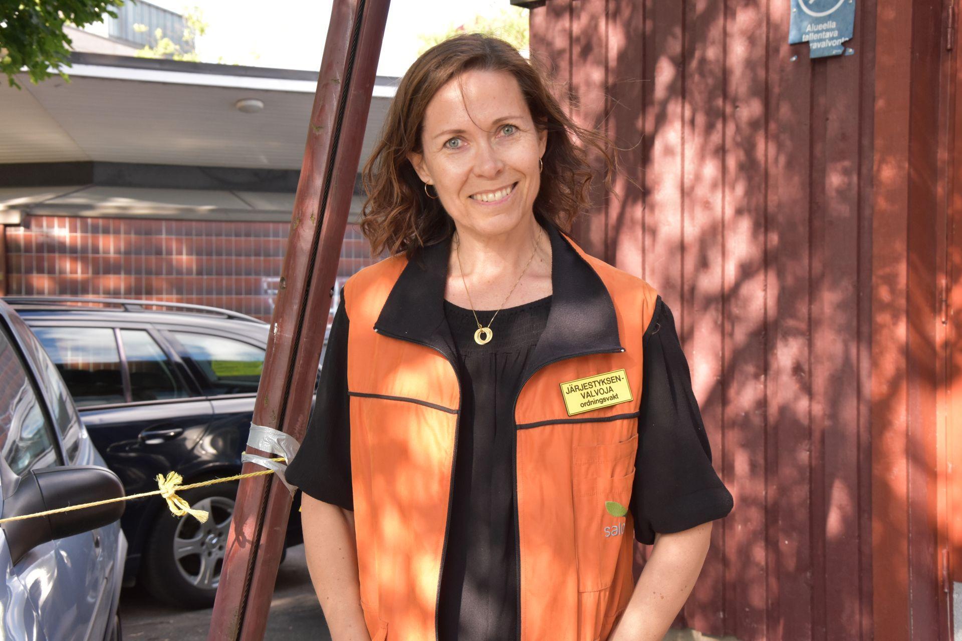En kvinna i en orange säkerhetsväst lär in i kameran.