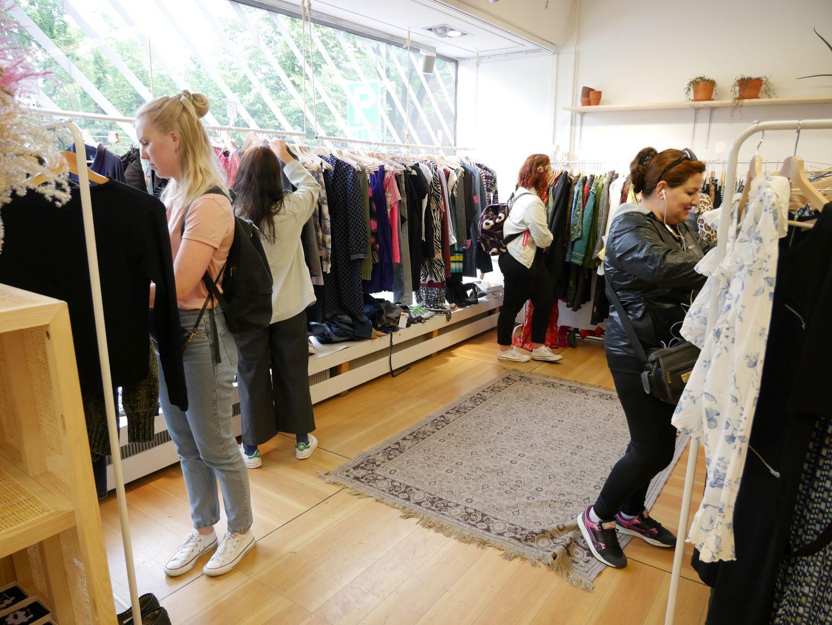 folk kollar in kläder på loppmarknad