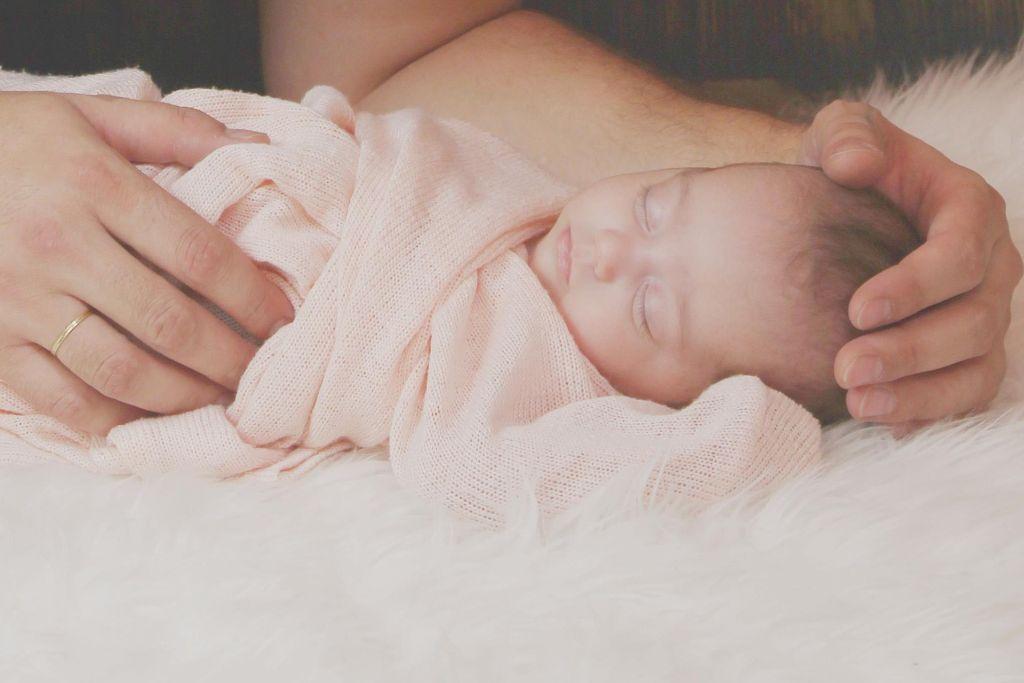ett nyfött barn ligger inlindad i en filt och sover. Ett par vuxna händer håller om barnet.