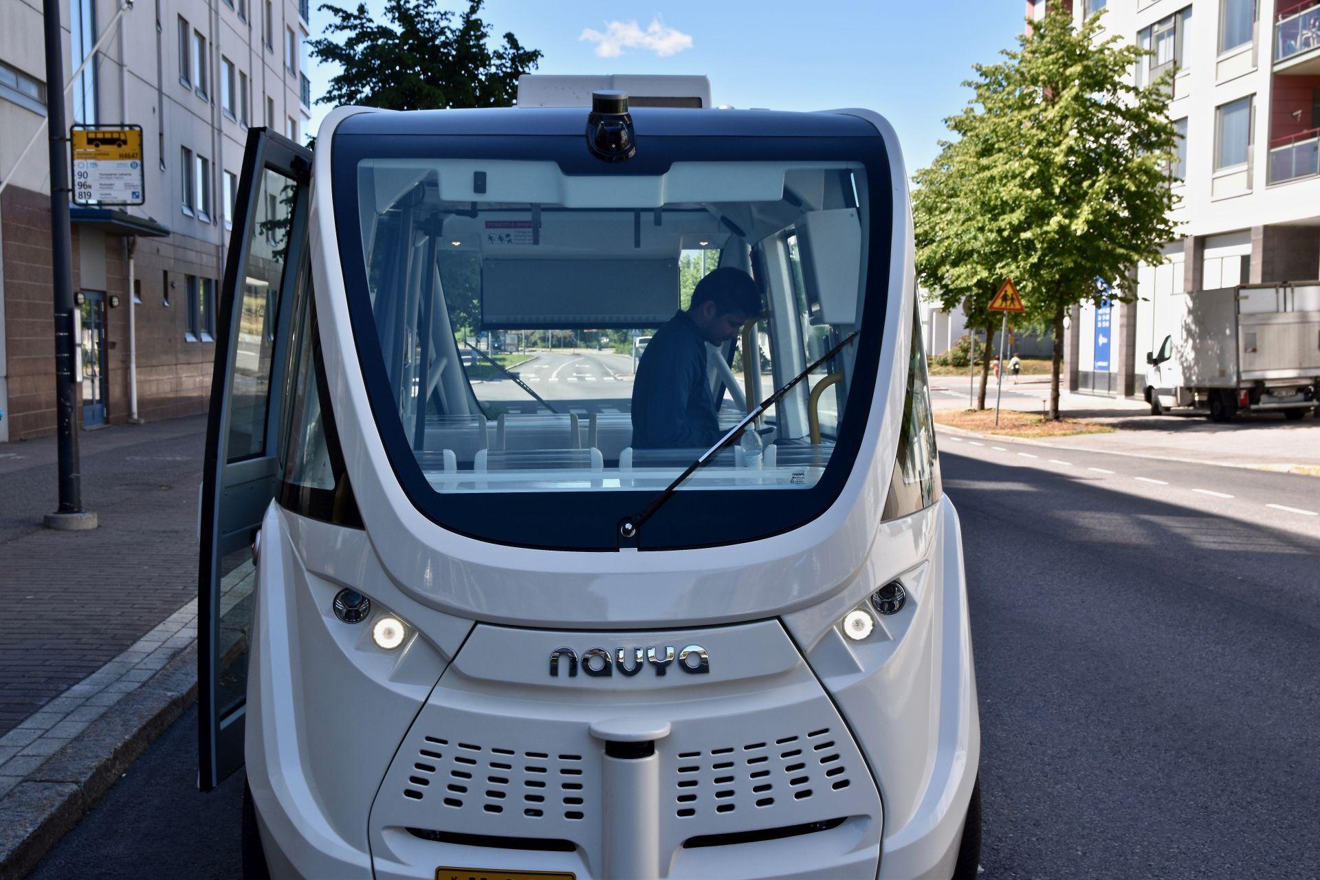 En grå självkörande buss i på en gata i Helsingfors.