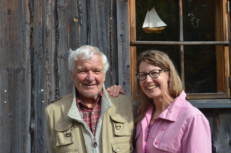 Glad man och kvinna framför gammal trävägg