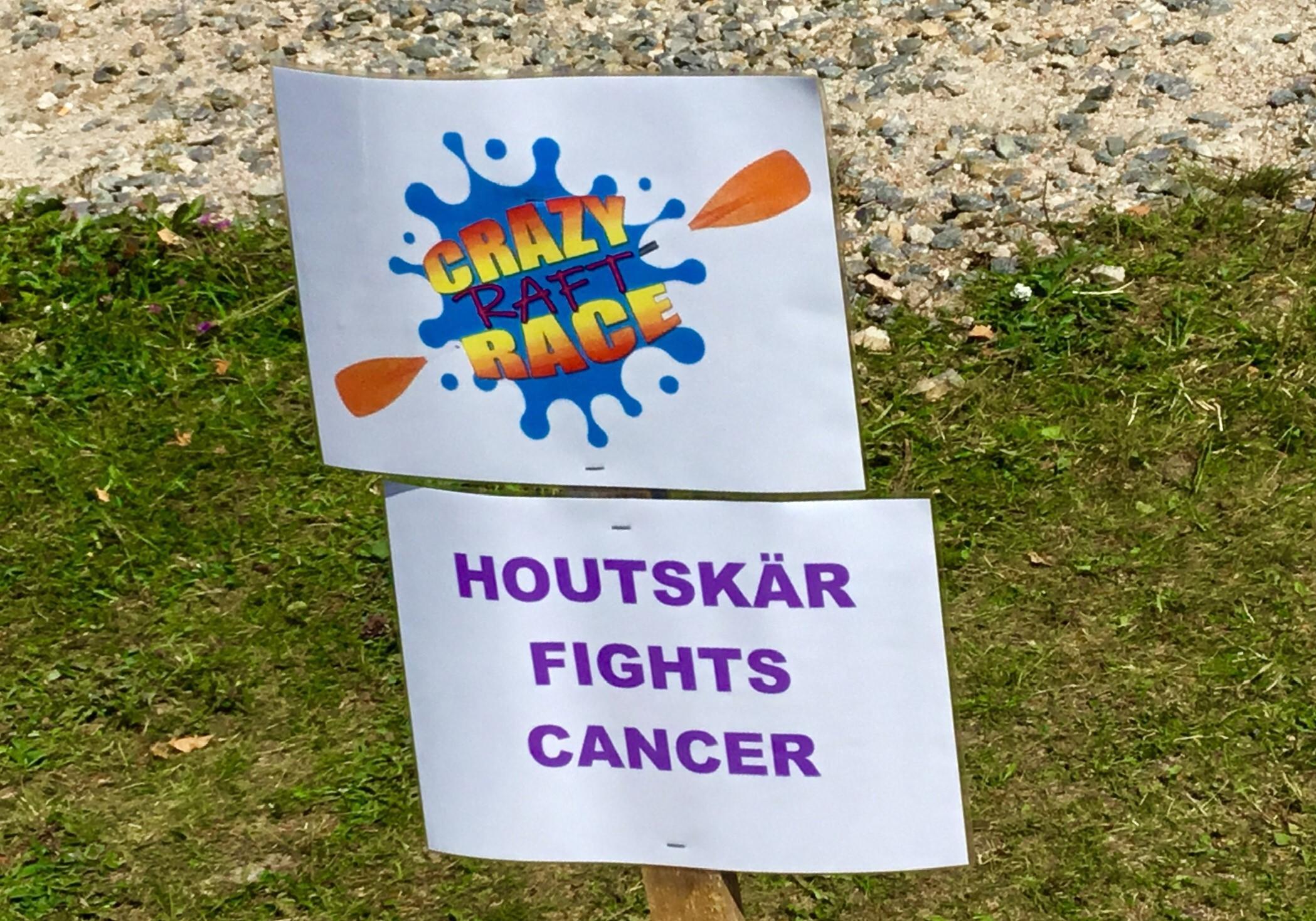 """En skylt med texten """"Crazy raft race"""" och """"Houtskär fights cancer"""""""
