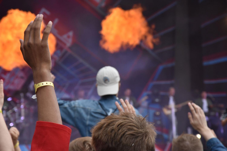 en man sitter pånågon axlar i publiken på en konsert. På scenen ser man pyroteknik