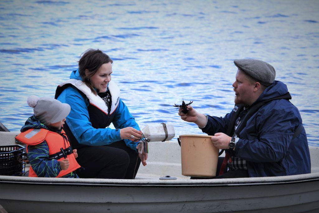 En kvinna, en man och ett barn sitter i en båt. Mannen håller i en kräfta.