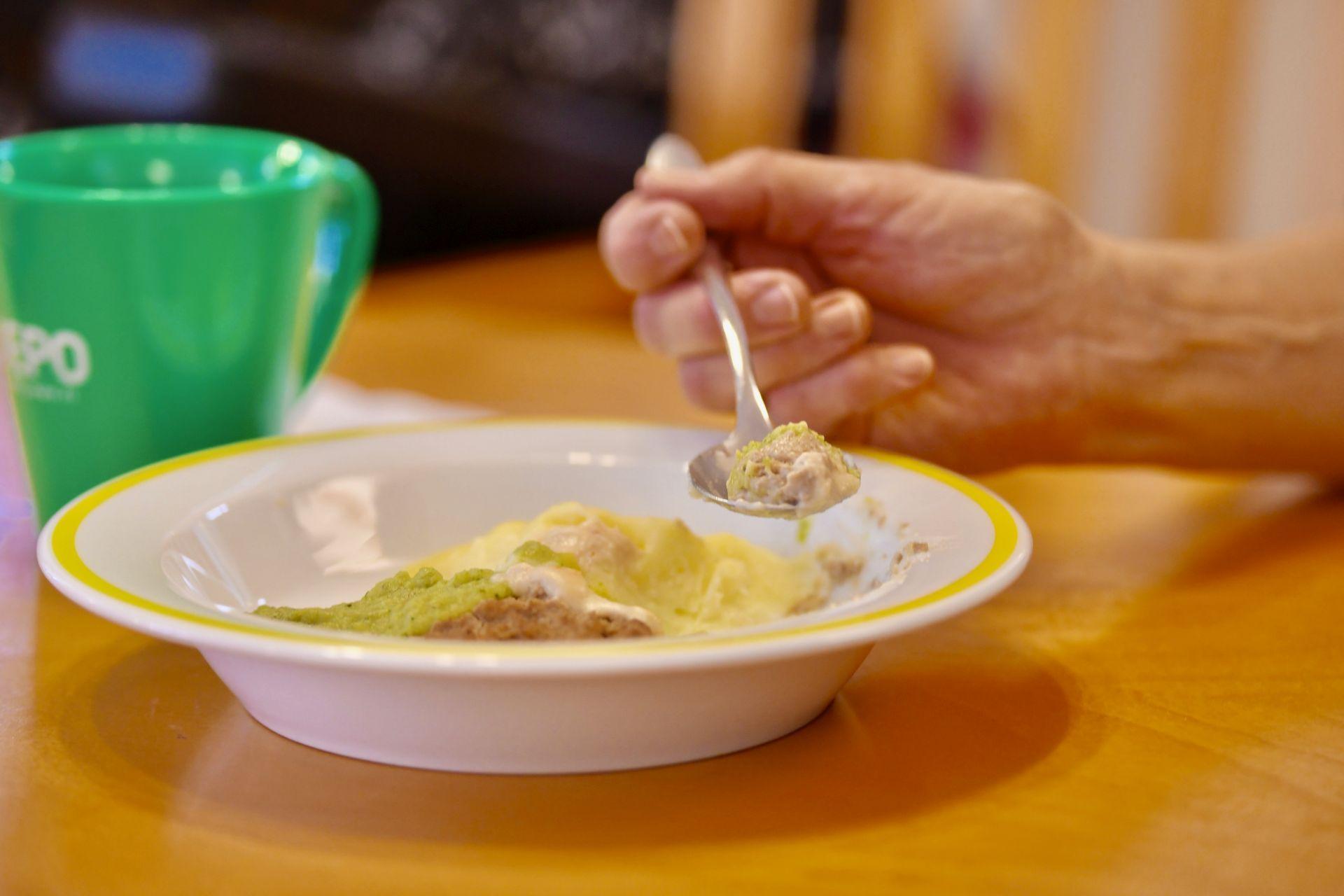 En tallrik med gröt och en hand som håller i en sked.