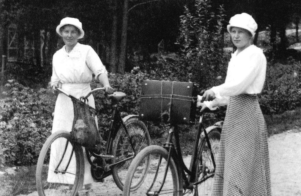 Ett svartvitt fotografi av två kvinnor som leder varsin cykel.