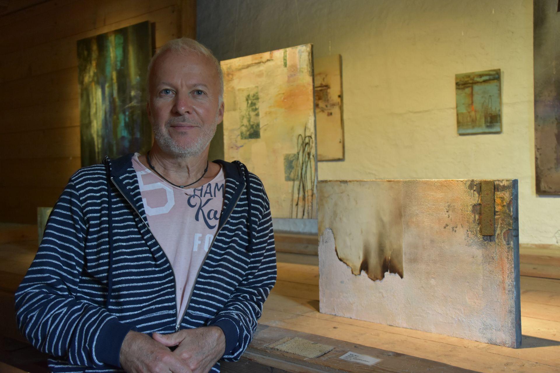 En man står lutad på ett bord bredvid en abstrakt tavla som går i beige och rostiga toner.