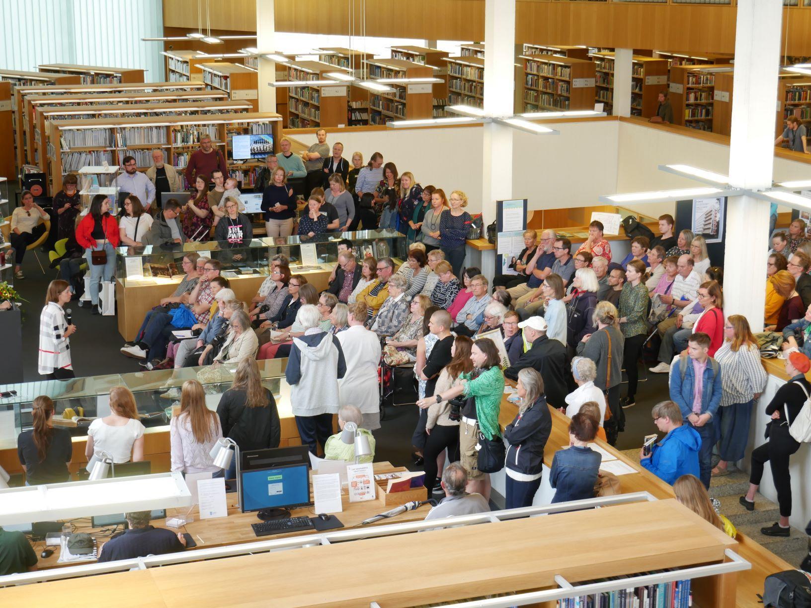 Li andersson talar inför en stor folksamling i biblioteket