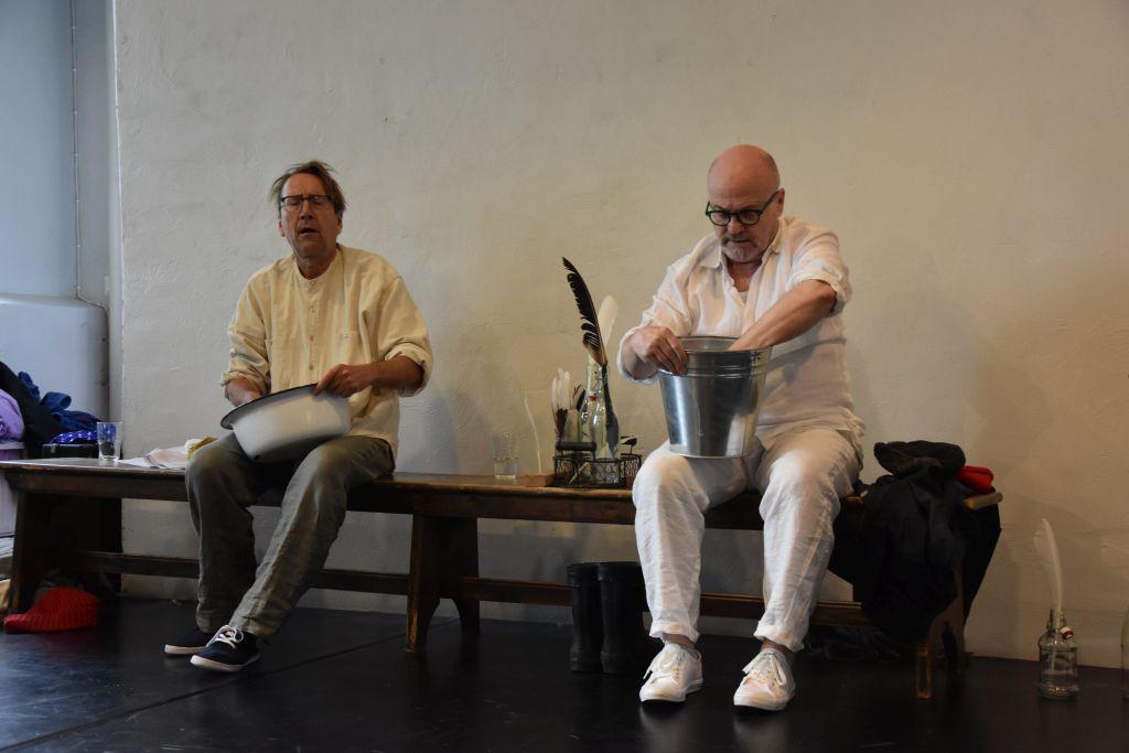 två män klädda i kläder gjorda av naturfiber sitter på en bänk med gamla emaljkärl.
