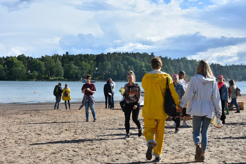 folk i regnkläder går längs en solig strand