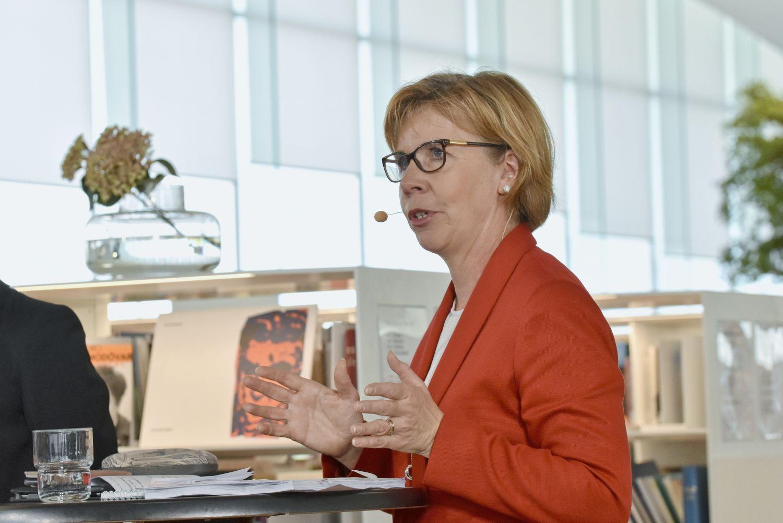 Porträtt av vit kvinna som står och pratar.