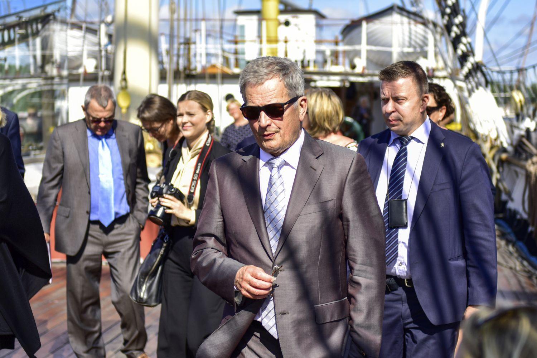 Sauli Niinistö iklädd kostym och solglasögon. I bakgrunden syns en hel del andra människor.