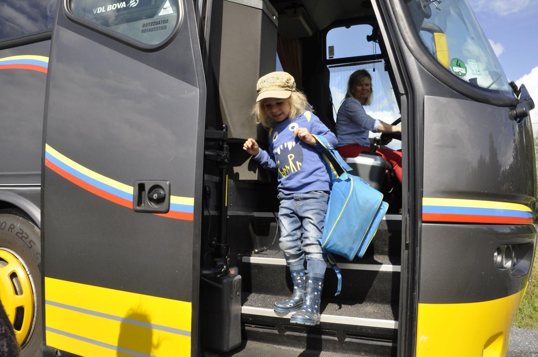 Förskolpojke stiger ut ur buss.