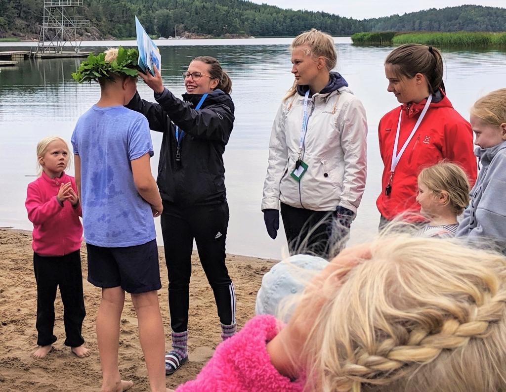 Barn och vuxna är samlade på en strand. En vuxen kvinna lägger en blomkrans på en pojkes huvud.